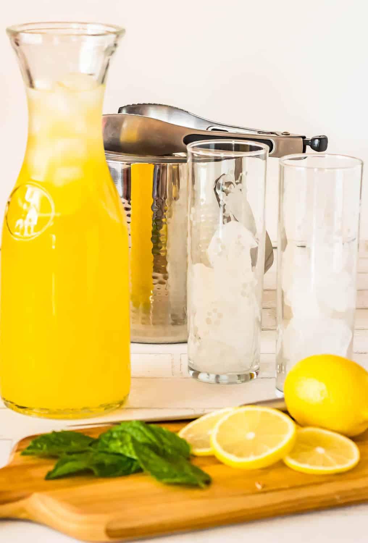 Pisco Lemonade with Lemongrass and Mint - a carafe with pisco lemonade, 2 glasses with ice, lemon, mint, ice bucket.