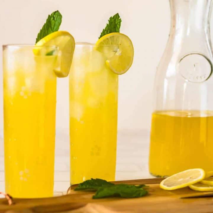 2 glasses of pisco lemonade and a carafe half full.
