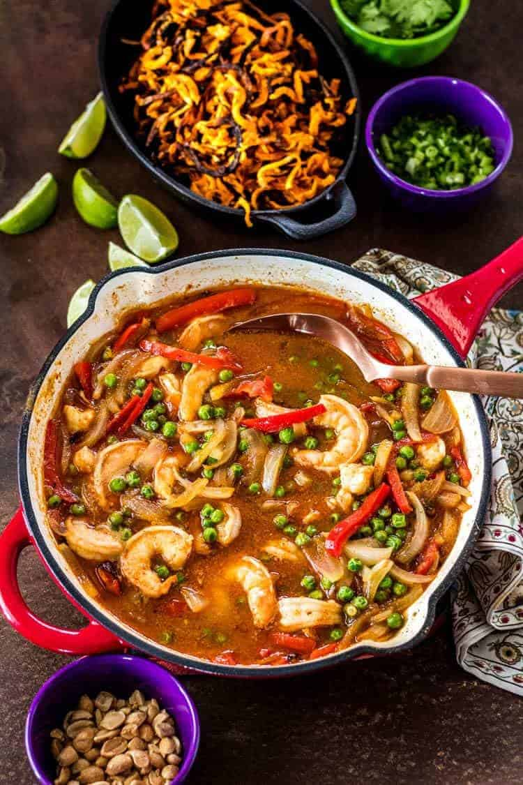 Thai Sweet Potato Noodle Bowls with Shrimp and Peas - A red cast iron skillet with the prepared Thai curry.