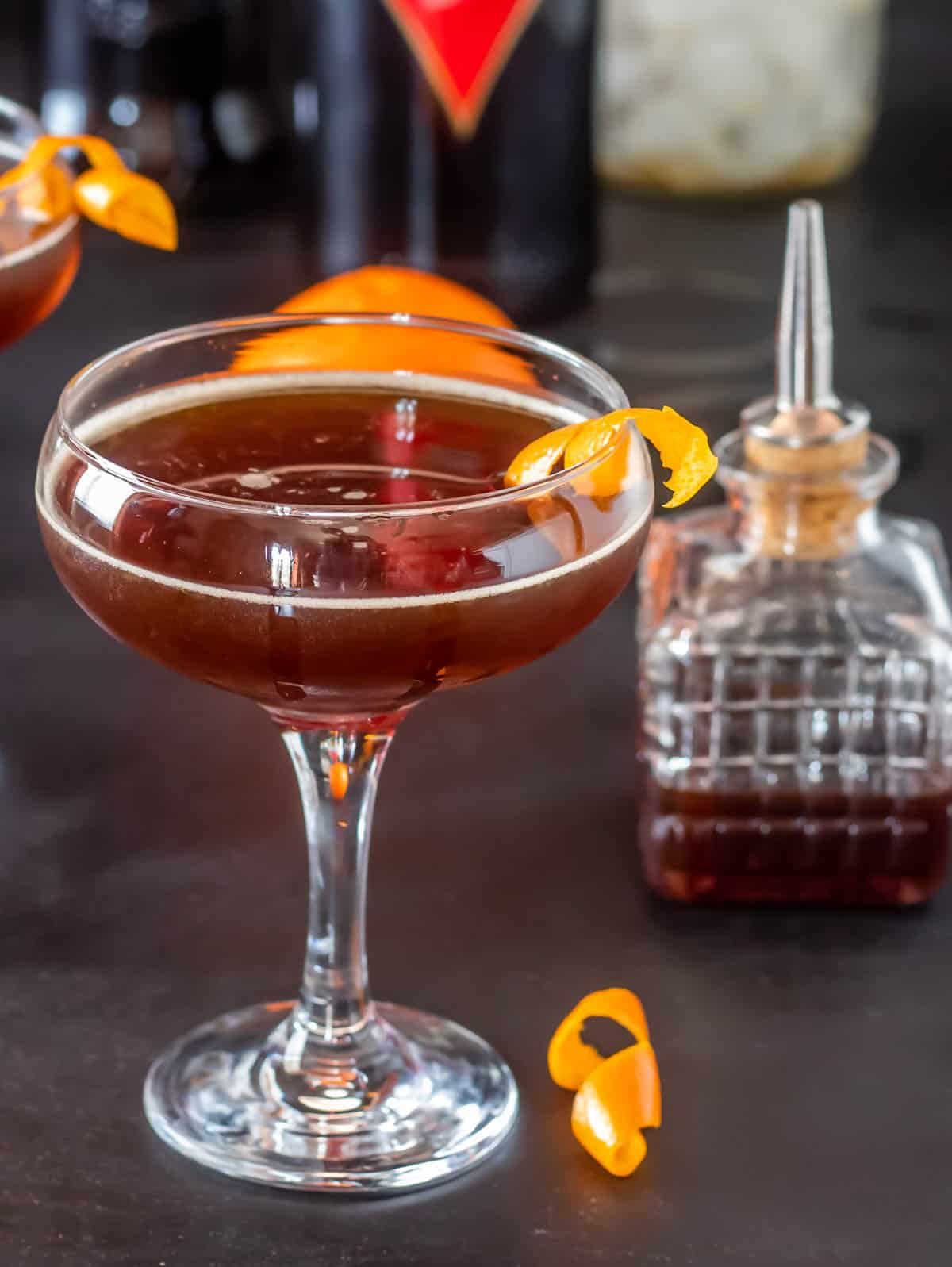 A single coupe glass with a red vermouth and Cynar cocktail with an orange twist.