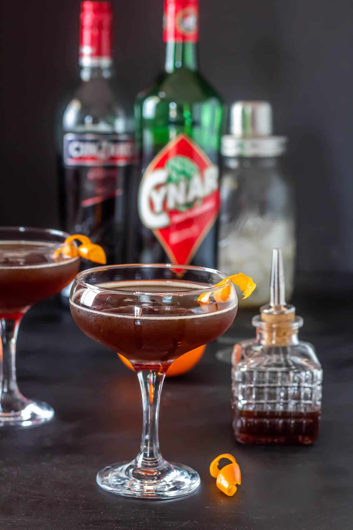 Mid-Summer's Night Cynar and Vermouth Cocktail - a dark mahogany cynar and vermouth cocktail in a coupe glass with a bottle of Cynar in the background.