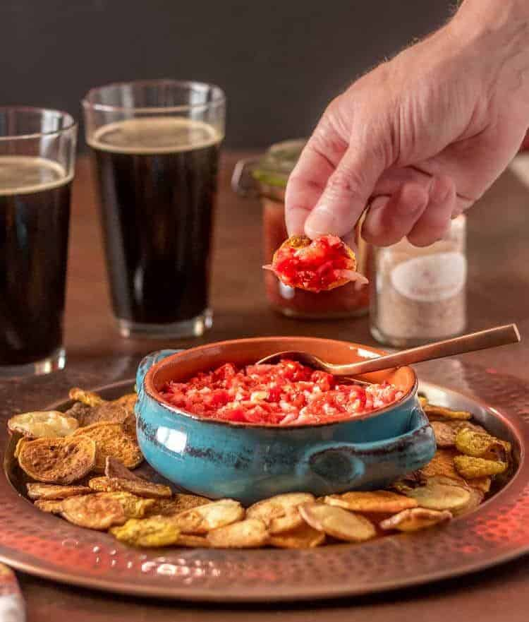 Fermented Peruvian Red Pepper Salsa - a scoop of salsa on a chip with 2 beers in the background.
