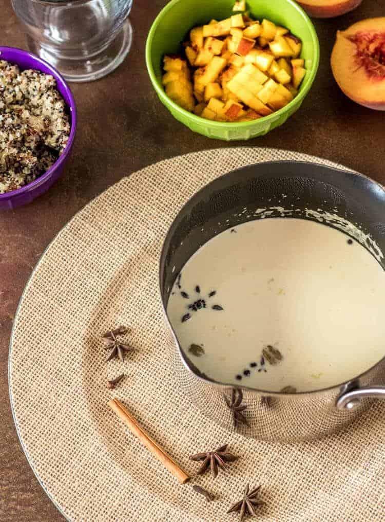 Peruvian Quinoa Porridge with Peaches - a small saucepan with spice infused milk, diced peaches in a green bowl, and quinoa in a purple bowl.