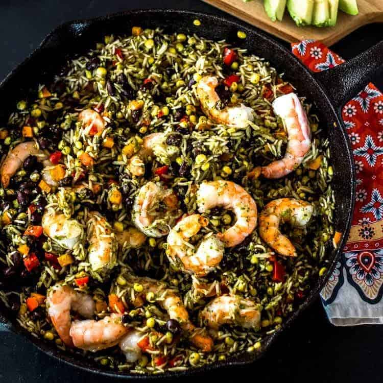 Mexican Arroz con Camarones (Rice and Shrimp) in a cast iron skillet with a red patterned napkin.
