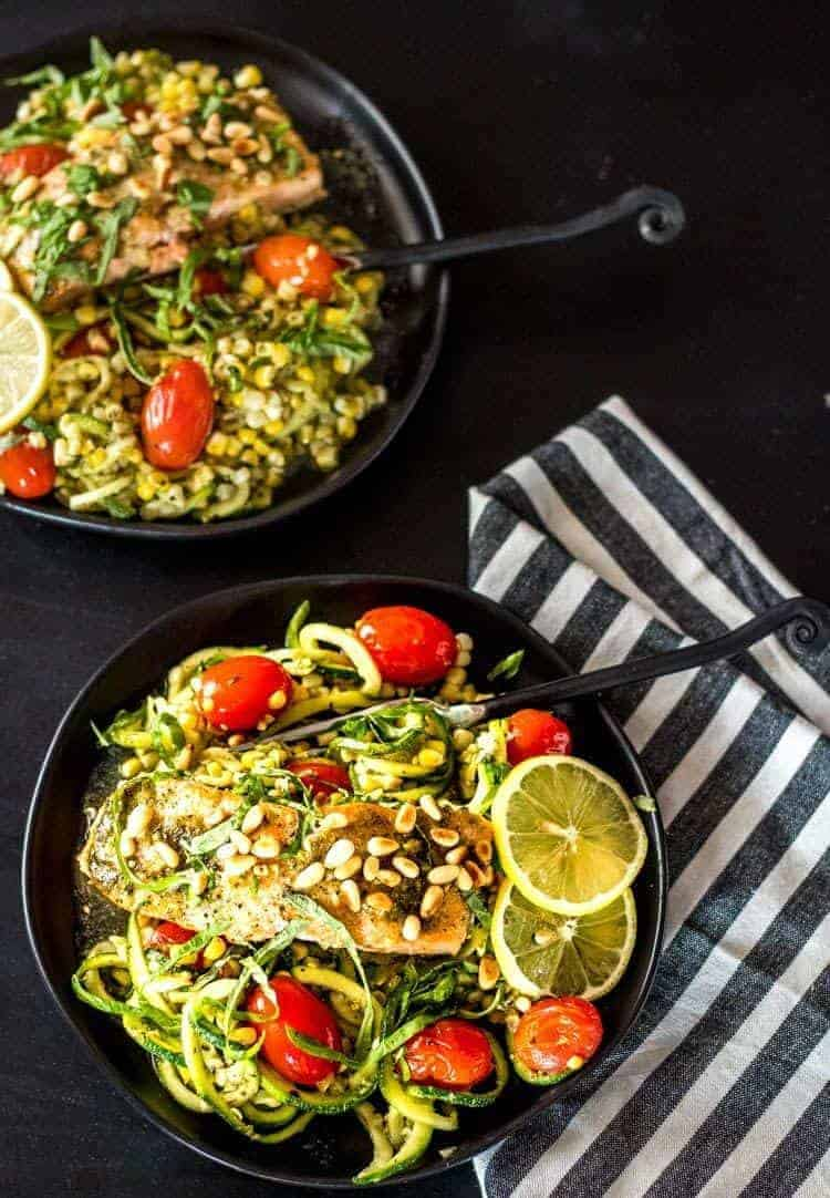 Pesto Salmon and Zoodles in Parchment on a round black plate with a striped napkin.