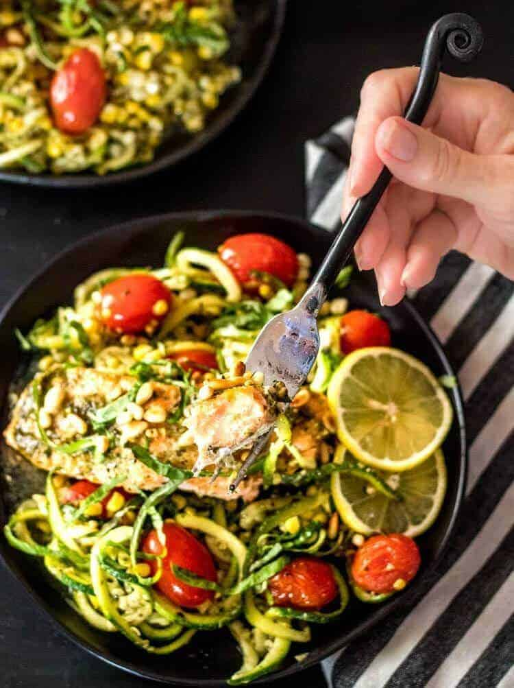 Pesto Salmon and Zoodles in Parchment a bite of salmon on a fork in my hand.