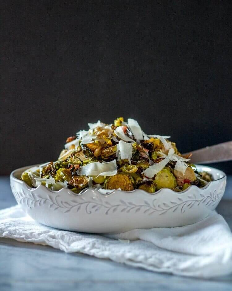 Roasted Shredded Brussels Sprouts with Pancetta and Pecorino piled high in a white ceramic bowl with a black background