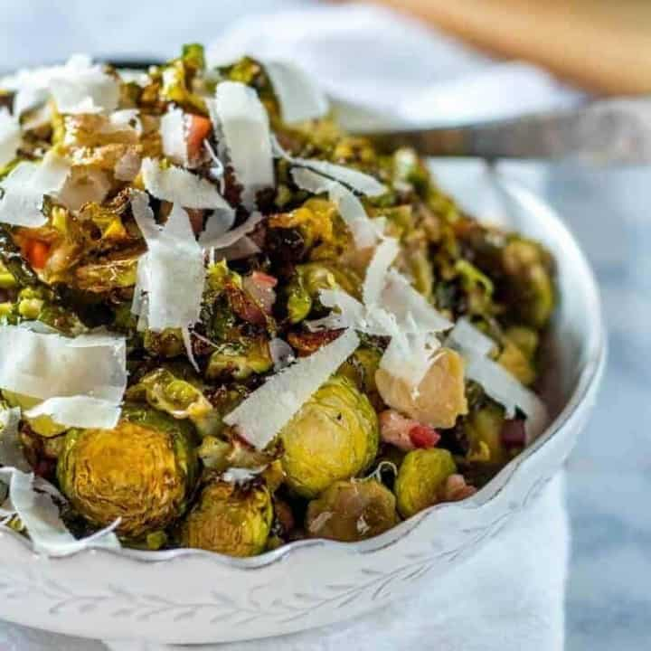 Shredded and Roasted Brussels Sprouts with Pancetta and Pecorino in a white bowl with a silver spoon and white napkin.