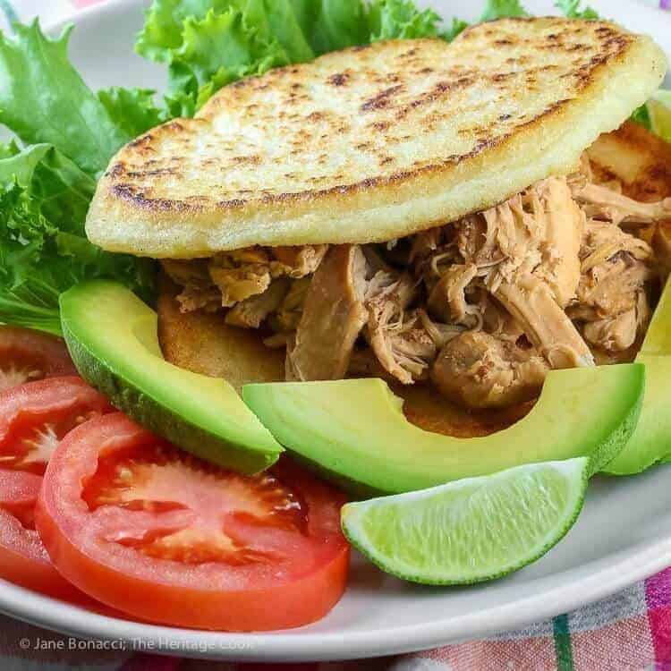 Instant Pot Chicken Filled Arepas on a white plate with avocado, lime, tomato.