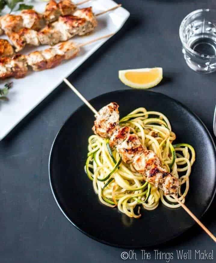 Puerto Rican pinchos de pollo marinated chicken kebabs on a black plate over zucchini noodles.