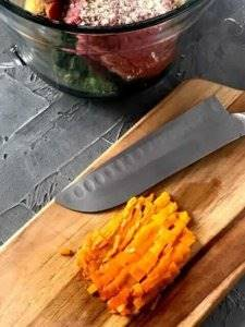 Aji amarillo on a wood cutting board with a knife for chopping.