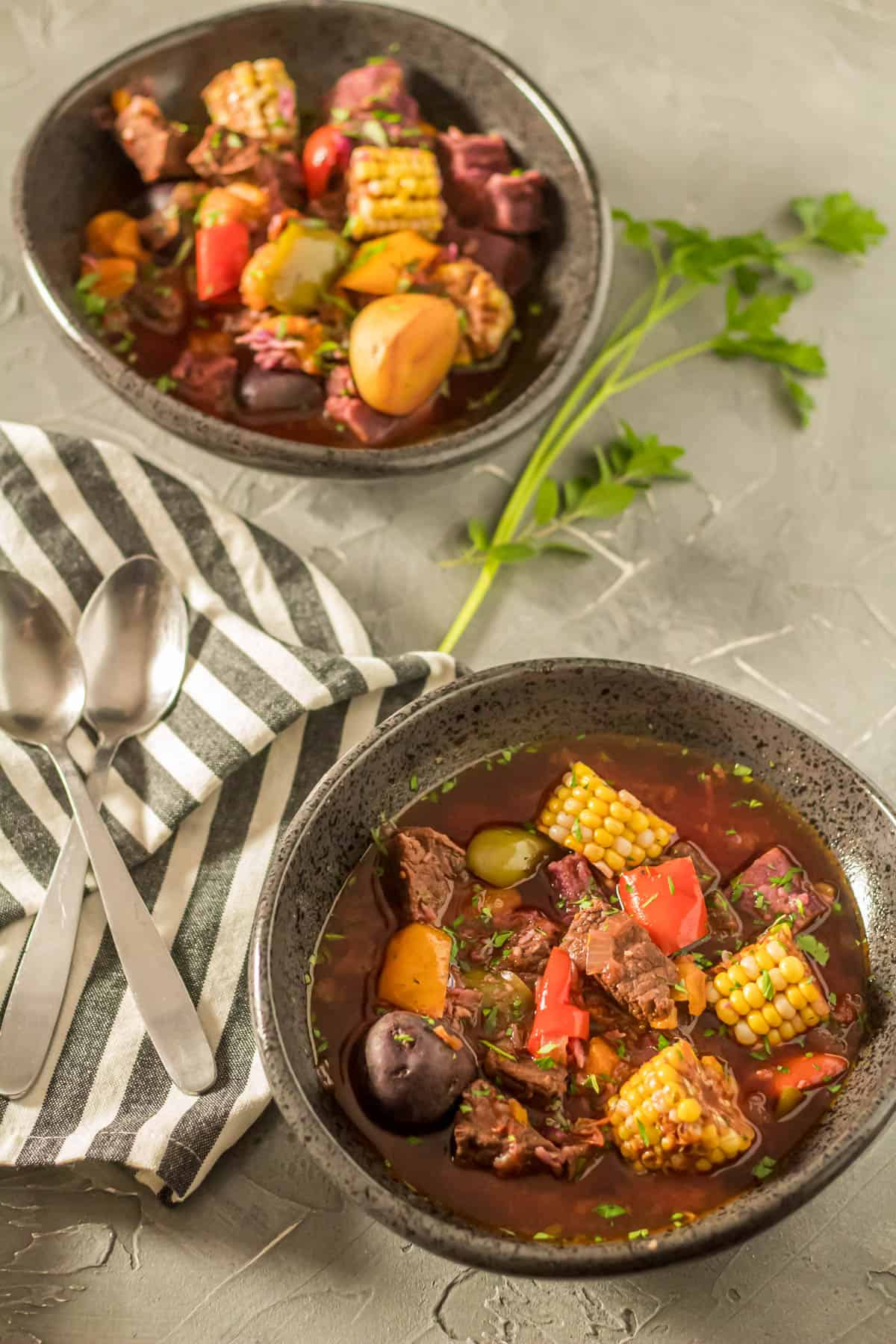 Instant Pot Argentinian Beef Stew (Carbonada Criolla) in a black handmade ceramic bowl with a striped napkin.