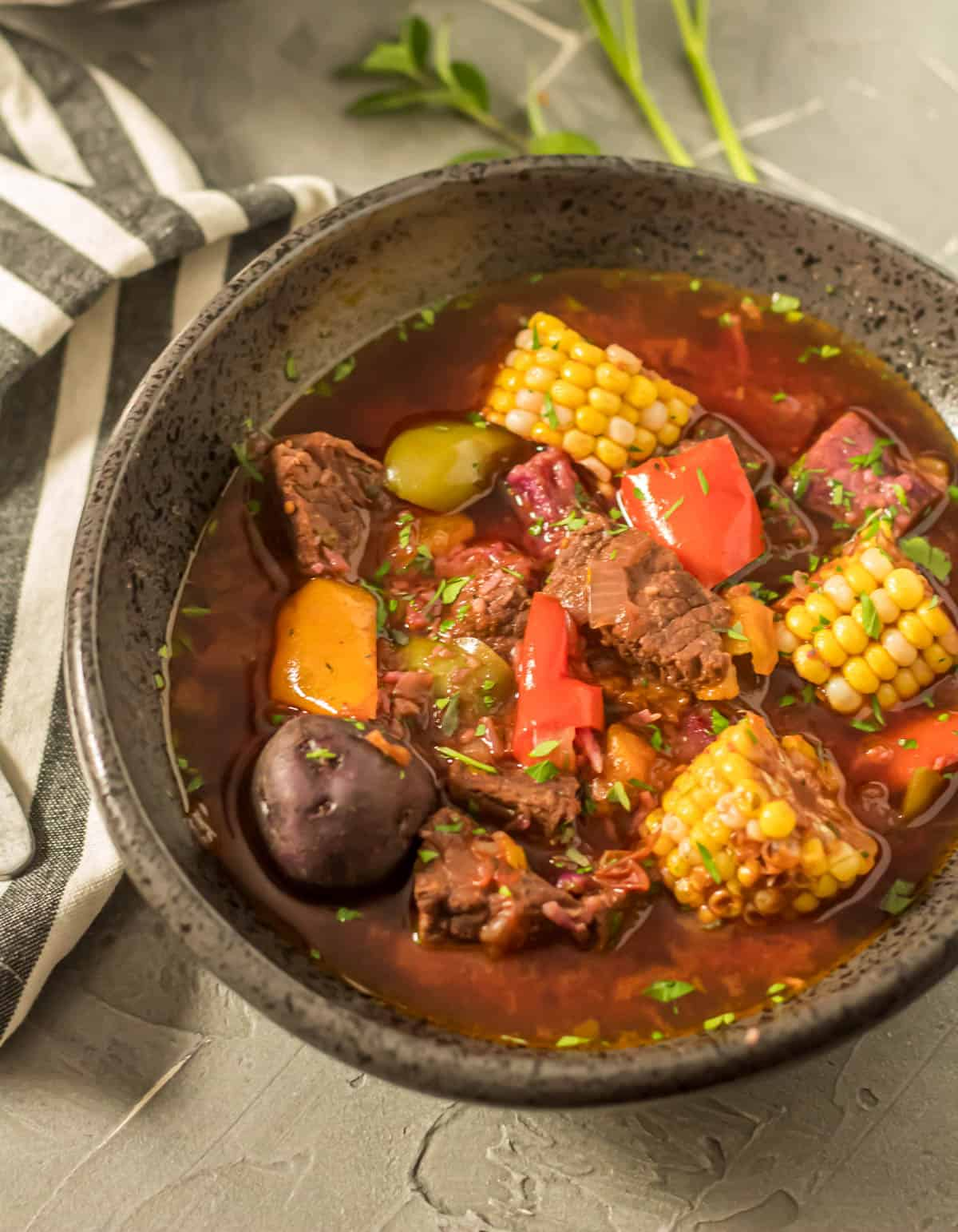 Instant Pot Argentinian Beef Stew (Carbonada Criolla) in a black stoneware bowl with a striped napkin. A close up view.