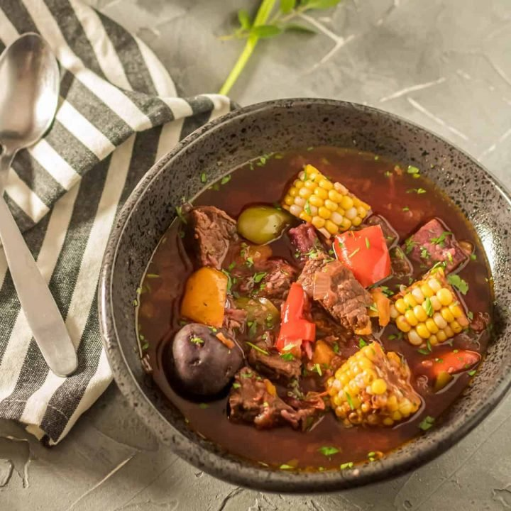 Instant Pot Argentinian Beef Stew (Carbonada Criolla) in a black bowl with herbs.