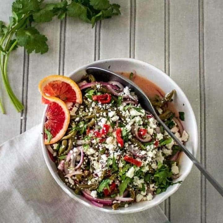 Nopalitos Salad with Citrus Vinaigrette in a white bowl with a twist of blood orange and fresh cilantro.
