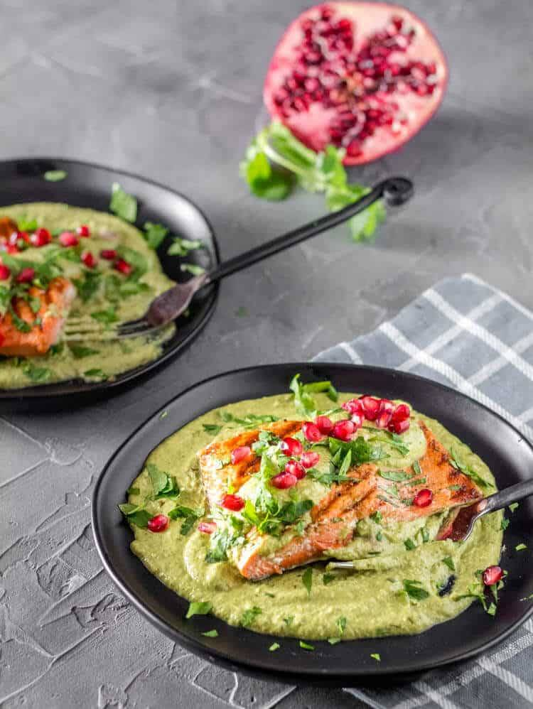 Fish in Tomatillo Cream Sauce on a round black plate with a grey napkin.