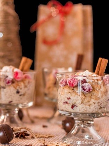 Gluten free Instant Pot Puerto Rican Rice Pudding (Arroz con Dulce) in clear glass trifle bowls with a cinnamon stick and candied cranberries.