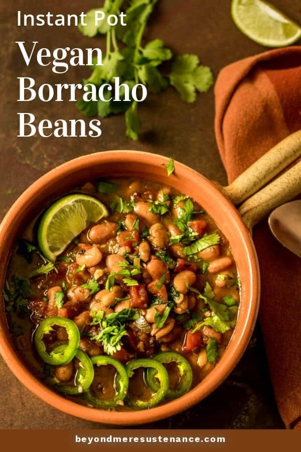 Instant Pot vegan gluten free borracho beans in a terra cotta bowl with a handle, orange napkin, cilantro lime wedge.