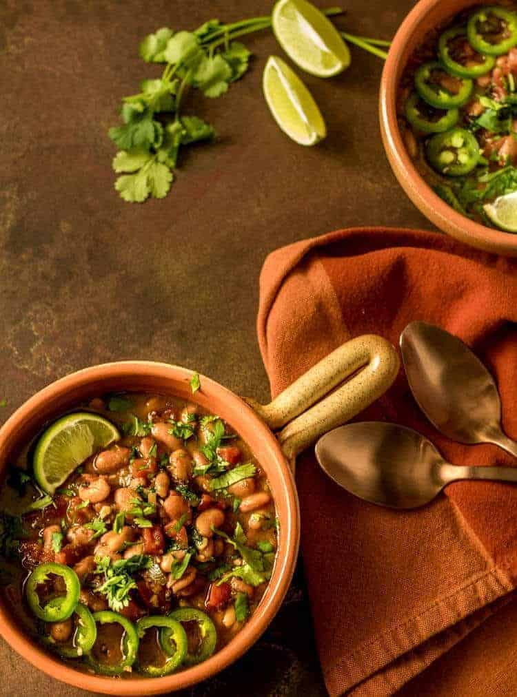 Instant Pot Vegan Borracho Beans in an orange stoneware bowl with a handle, copper spoons, and orange napkin.
