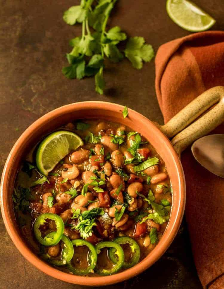 Instant Pot Vegan Borracho Beans close up with lime and jalapeños.