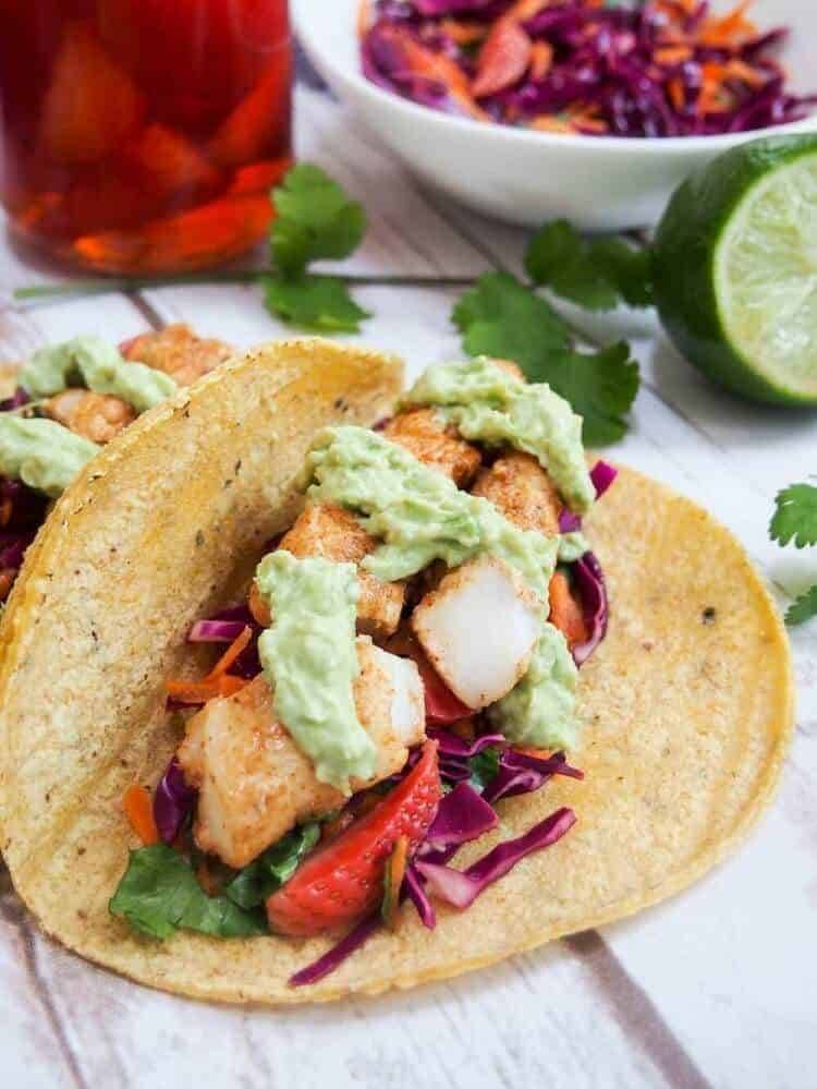 Cod Tacos with Pickled Strawberry Slaw in a corn tortilla with cilantro sprigs and lime.