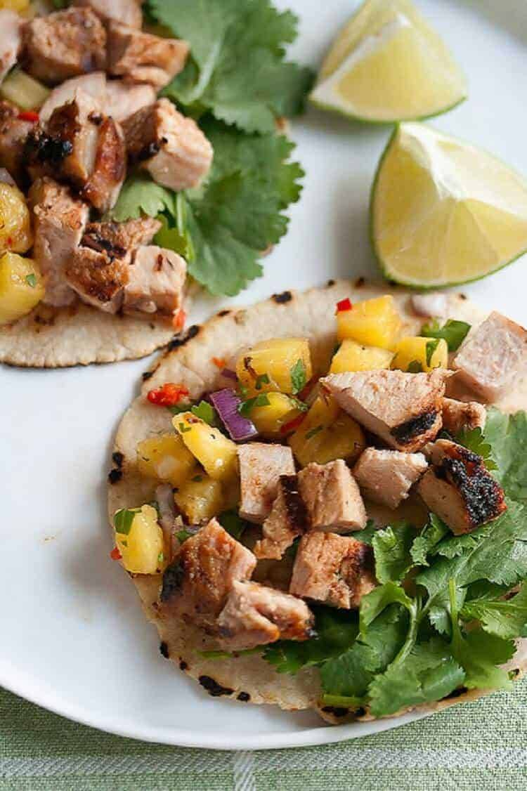 Grilled Pork Tacos with Pineapple Salsa and a lime wedge.