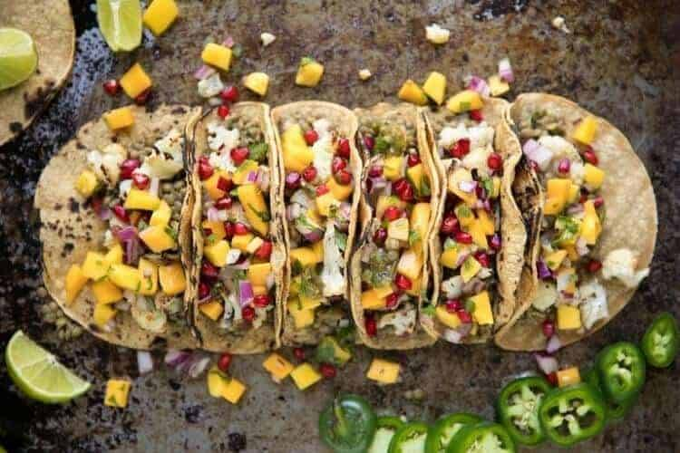 Lentil Tacos with Roasted Cauliflower and mango pomegranate salsa on a rustic tray.