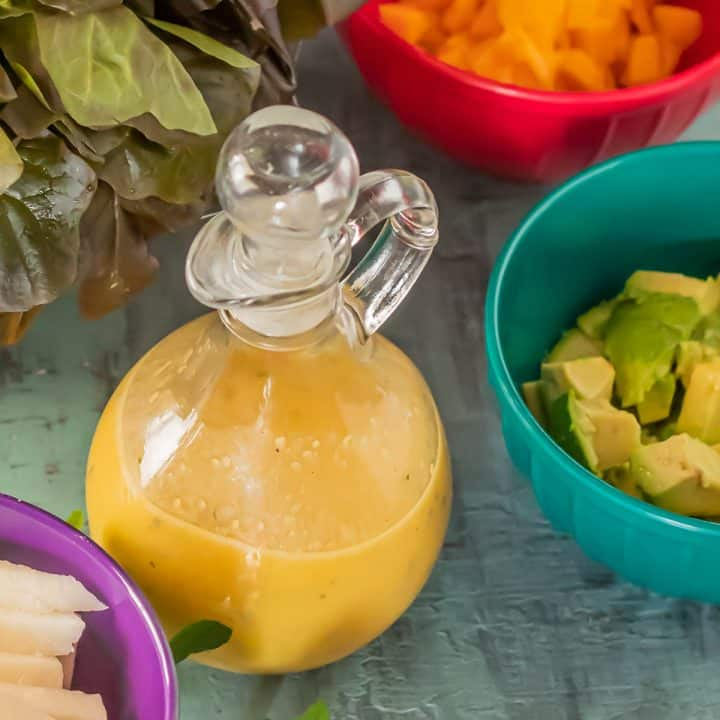 Passion Fruit Vinaigrette in a glass cruets with salad ingredients.