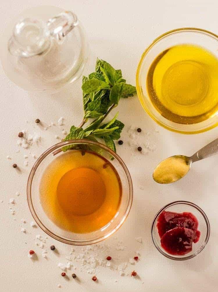 An empty glass cruet with fresh mint, olive oil, dijon mustard, raspberry preserves, raspberry blush vinegar, flake sea salt, and pepper corns.