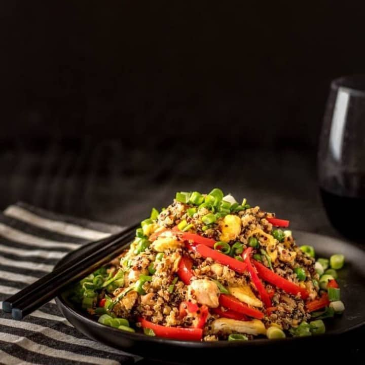 Quinoa Chaufa with chicken on a black plate with black chopsticks, a striped napkin, and a glass of wine