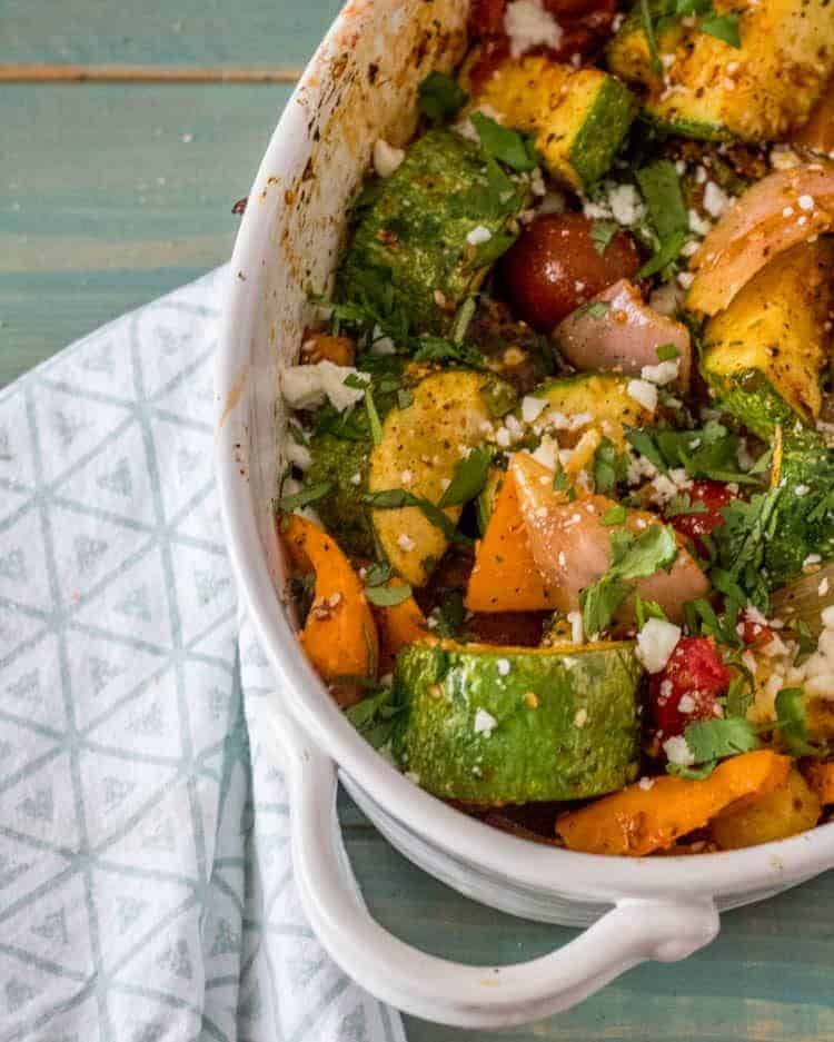 Chipotle Pepita Salsa on roasted veggies in a white oval baking dish and print napkin.