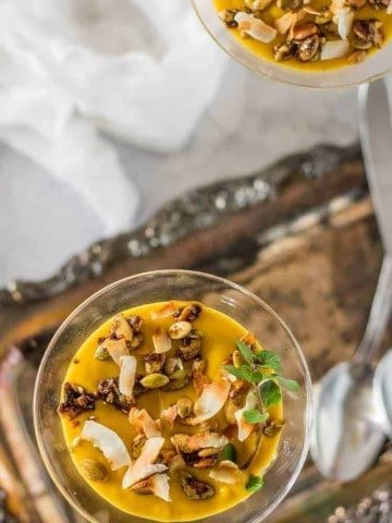 Coconut Mango Custard close up in a martini glass with candied pepitas and toasted coconut.