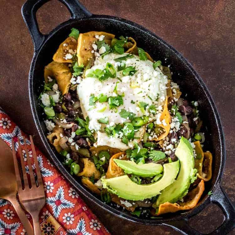 Vegetarian Green Chile Chilaquiles in an oval cast iron dish with egg and avocado.