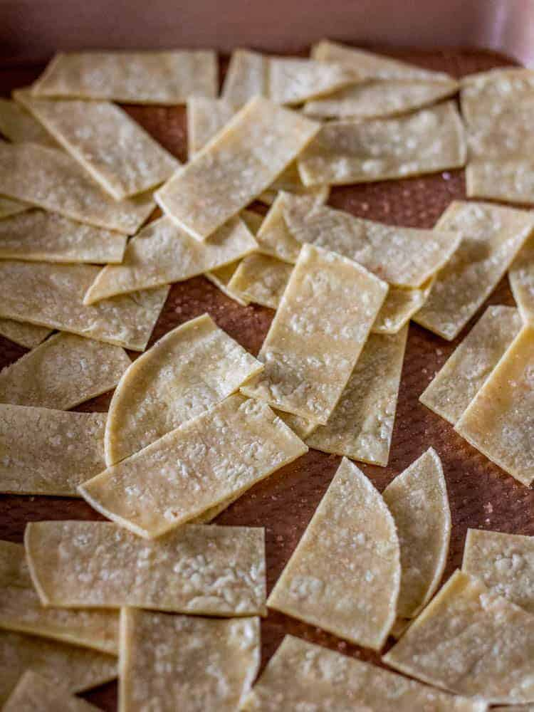 Tortilla strips with cooking spray and sea salt on a copper baking sheet.