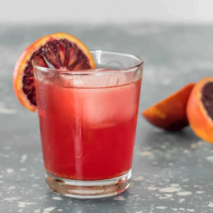 2 Blood Orange Mezcal Negronis in rocks glasses with a slice of blood orange.