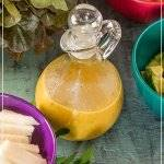 Passion Fruit Vinaigrette in a glass cruet with salad ingredients in brightly colored bowls.