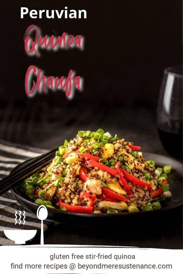 A black background with a black plate of Peruvian stir-fried quinoa with vegetables, chopsticks, striped napkin.