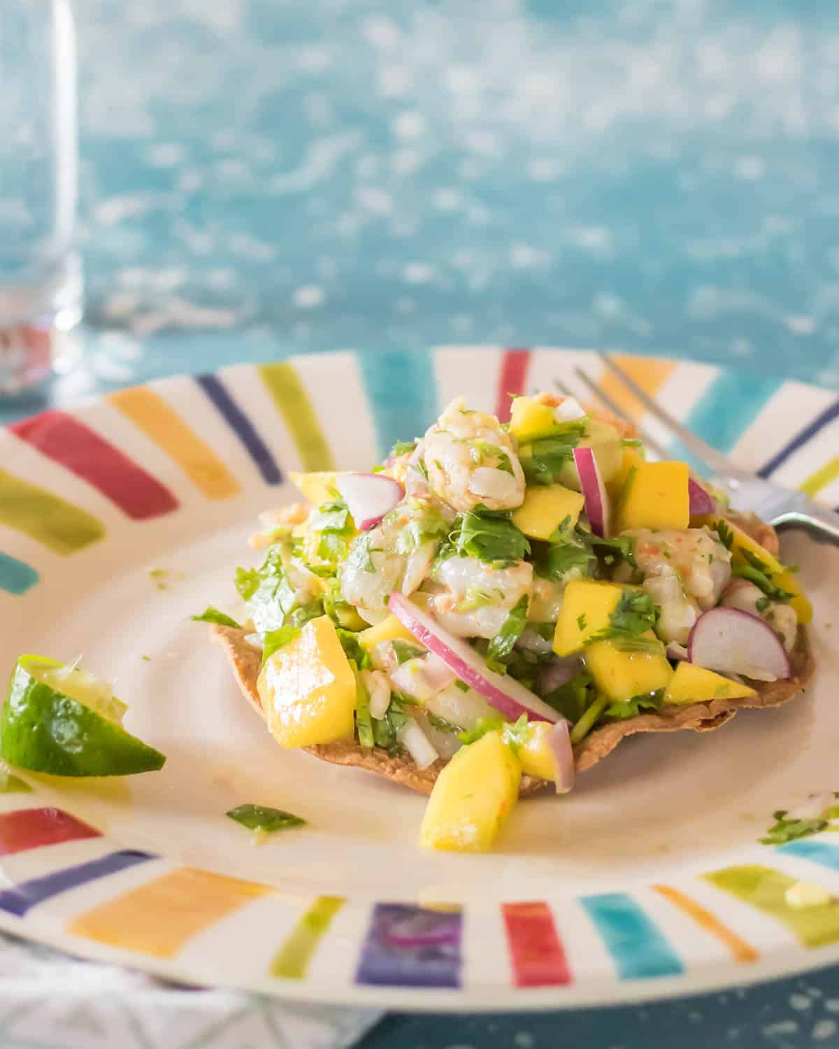 A Shrimp Ceviche Tostada with Mango and Avocado on a striped plate.