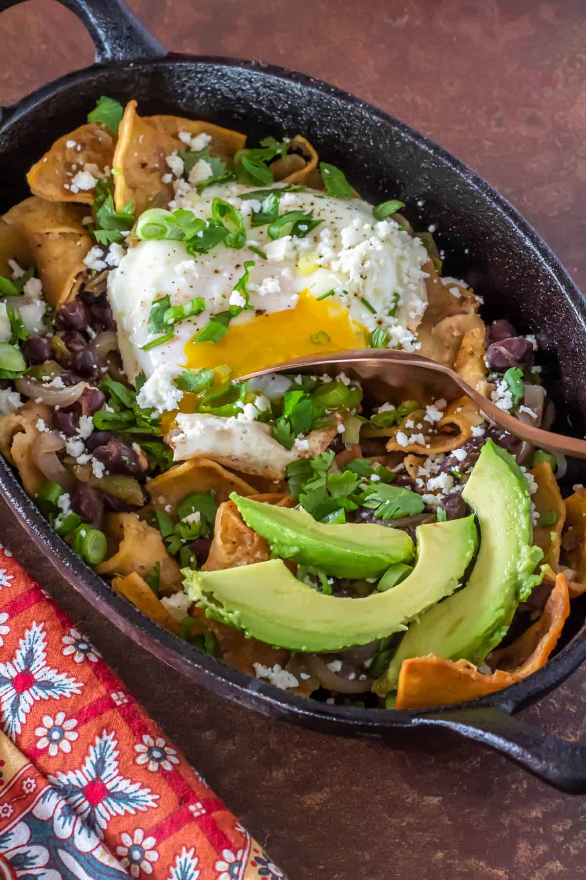 Green Chile Chilaquiles  with a runny egg and avocado in a cast iron dish.