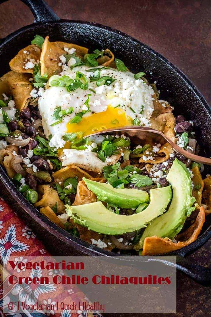 Chilaquiles in an oval cast iron single serving dish with avocado and basted egg.