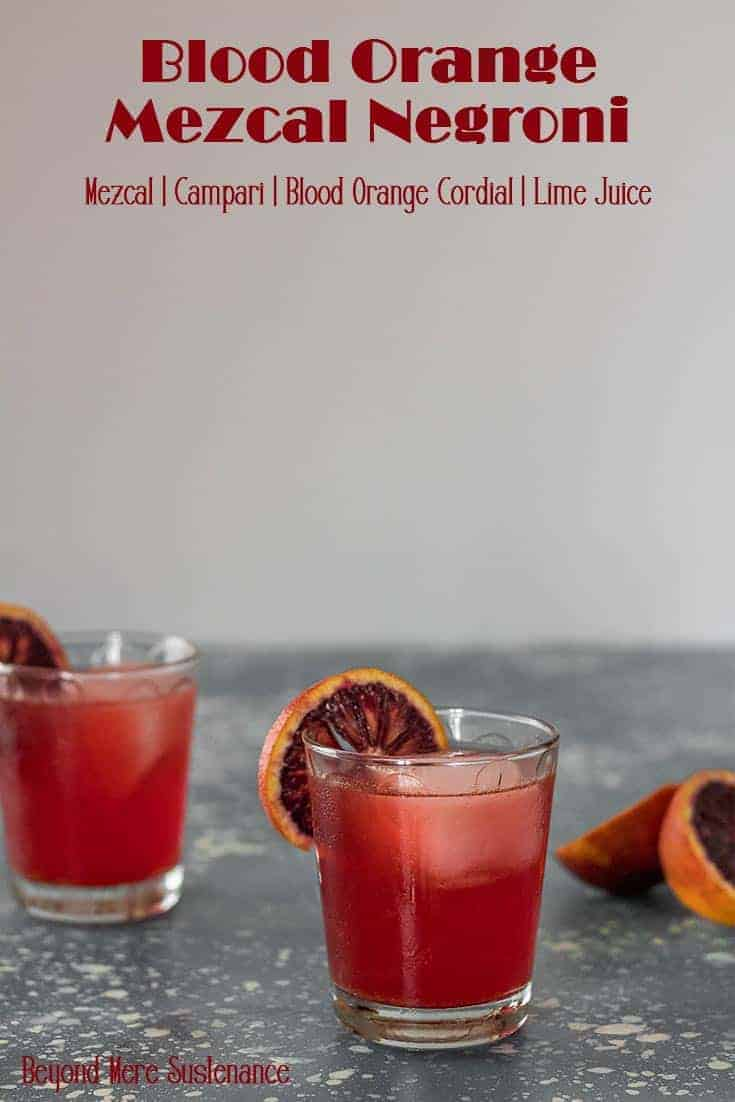 2 rocks glasses with a cocktail and slice of blood orange on a grey speckled background.
