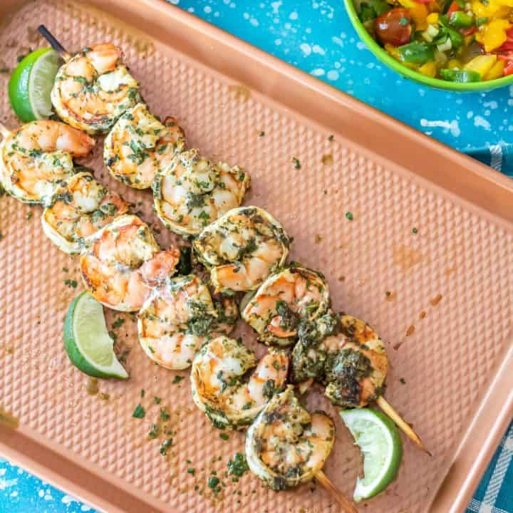 Spicy Cilantro Lime Shrimp Skewers on a copper baking sheet with lime wedges.