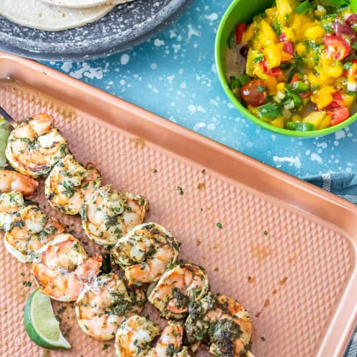 Spicy Cilantro Lime Shrimp skews on a copper baking sheet with lime wedges and mango-tomato salsa.