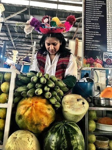 A Peruvian woman with tropical fruits for smoothies.