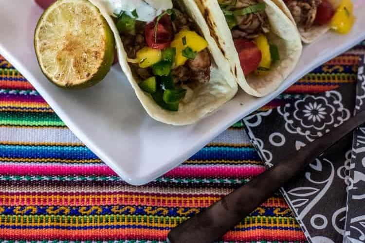 Indian Street Tacos with marinated shrimp, mango and tomato salsa, and cucumber raitta in flour tortillas on a striped table cloth.