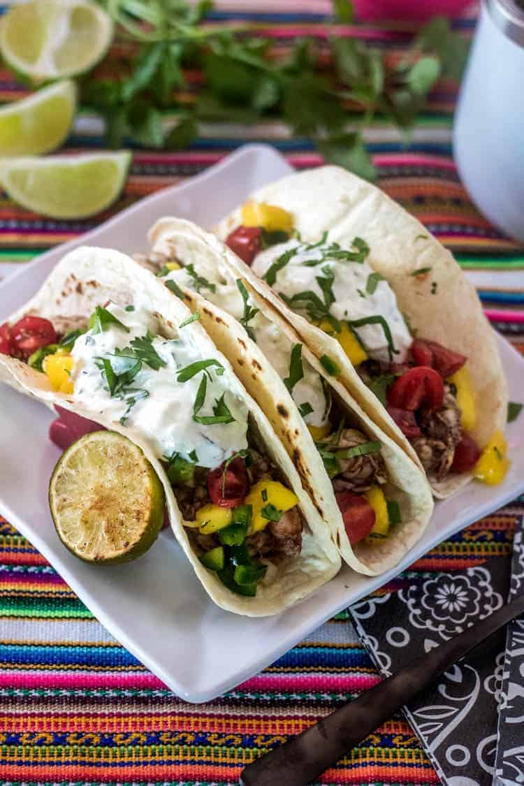 3 Indian Street Tacos with Grilled Shrimp topped with cucumber-mint raitta and mango and tomato salsa on a bright striped cloth with limes and cilantro.