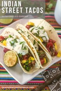 Indian Street Tacos with marinated shrimp, mango and tomato salsa, and cucumber raitta in flour tortillas.