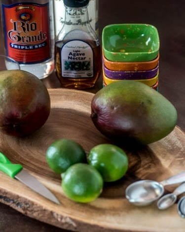 2 mangos, 3 limes, a knife, measuring spoons, tequila, triple sec, agave on a wood cutting board.