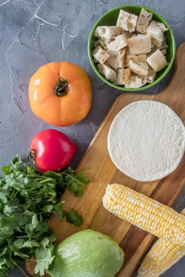 Ingredients for Grilled Mexican Panzanella Salad with Chayote from top clockwise: Bread cubes, queso fresco, corn on the cob, whole chayote, cilantro, heirloom tomatoes.