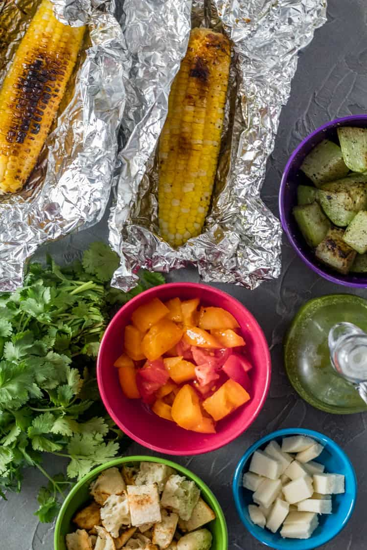 All of the ingredients for the Grilled Mexican Panzanella Salad with Chayote ready to be tossed. From top clockwise: Grilled chayote cubes in a purple bowl, Cilantro Lime Vinaigrette, queso fresco cubes, tomato cubes, cilantro, grilled corn.